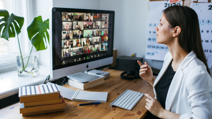 A woman sits in front of a computer monitor in her home office