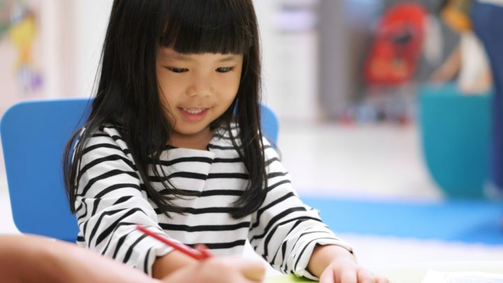 A small child sits at a table colouring