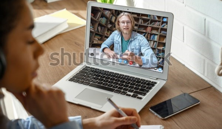 A girl sits in front of a laptop with a blond, bearded teacher on the screen